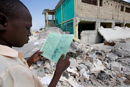 Хаитянски ученик разглежда ученически бележник, който намира в отломките на доскорошното си салезианско училище.